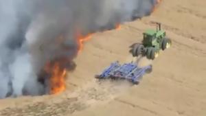 Cet agriculteur fait un coupe-feu avec son tracteur pour protéger son champ de blé