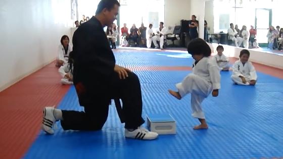 Un enfant essaie de casser une planche au cours de taekwondo