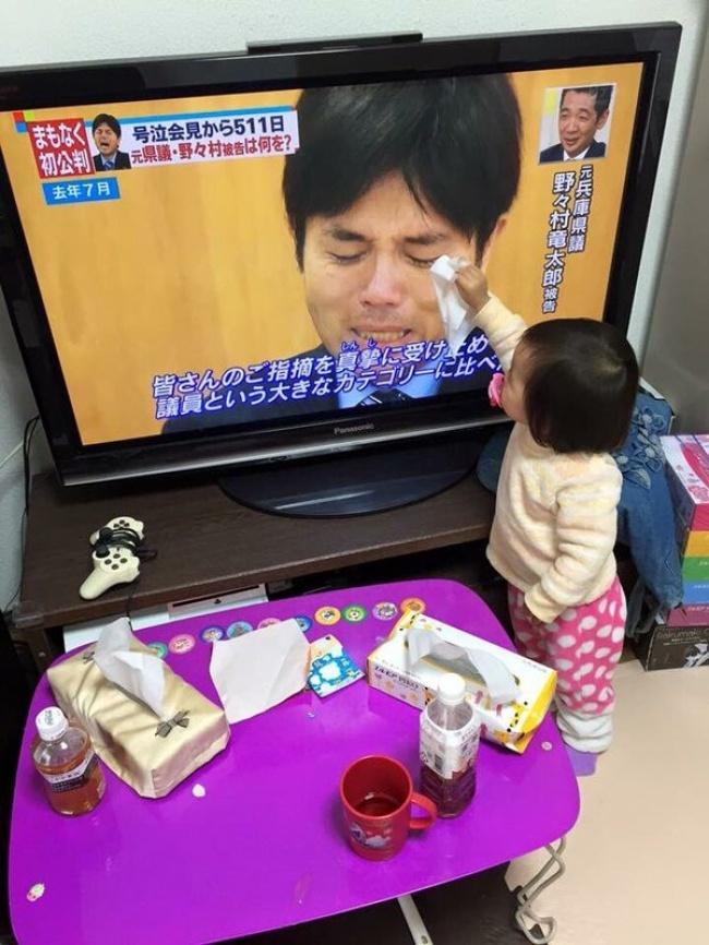 Un bébé qui tente d'essuyer les larmes d'un homme qui pleureà la télé