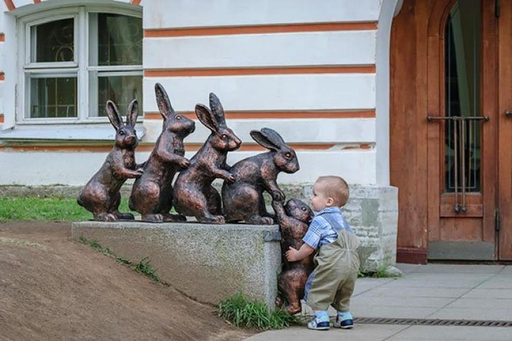 Un enfant aide un lapin à grimper une sculpture