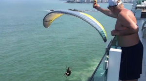 Un parapentiste attrape une bière depuis un balcon en plein vol