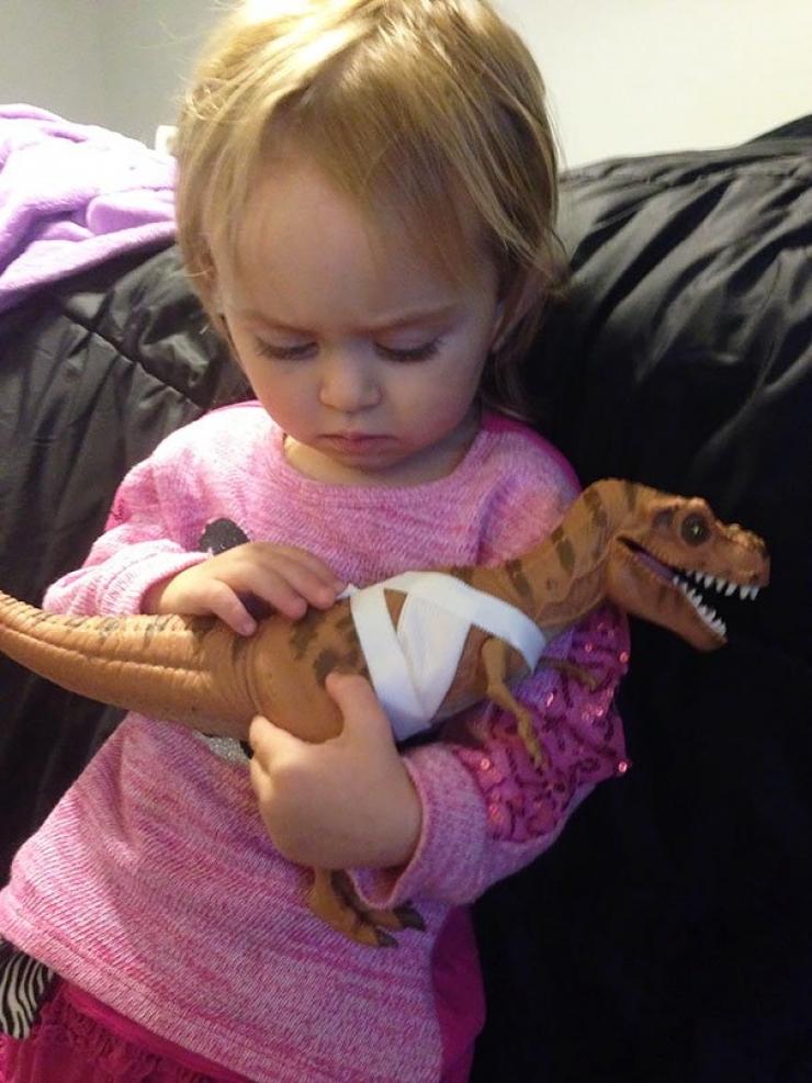 Une fille de 2 ans qui réconforte son dinosaure blessé