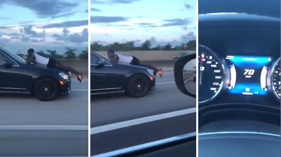 Une femme en train d'accélérer sur l'autoroute avec son ex accroché au pare-brise