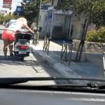 Une fille blonde tente de démarrer son scooter en appuyant sur la béquille