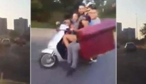 Il roule en scooter avec un canapé et deux personnes dessus à Paris
