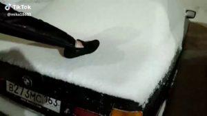 Un homme fait pipi debout sur une voiture recouverte de neige