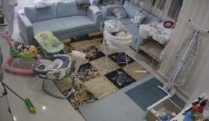 Une Baby-sitter sort un bébé de sa chambre avant l'effondrement du faux plafond
