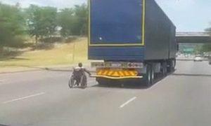 En fauteuil roulant, il s'accroche à l'arrière d'un camion qui roule sur l'autoroute