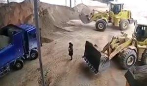 Le conducteur d'une tractopelle pelle et jette une femme dans le broyeur à sable !