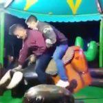 Deux amis montent sur un taureau mécanique
