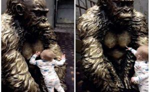 Un bébé essaie d'allaiter à partir d'une statue de gorille