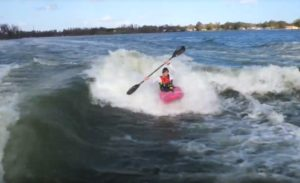 Un kayakiste prend une vague de sillage entre 2 bateaux sur un lac