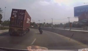 Un motard évite de se faire écraser par un camion conteneur