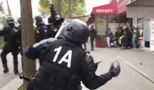 Un CRS jette un pavé sur les manifestants