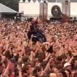 Les festivaliers soulèvent un homme en fauteuil roulant pour l'approcher de la scène