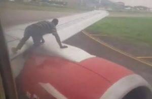 Un homme en train de monter sur l'aile d'un avion qui s'apprêtait à décoller