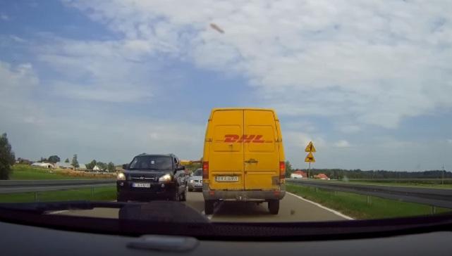 Un livreur donne un colis à un automobiliste