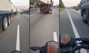 Un motocycliste en train de passer sous un camion