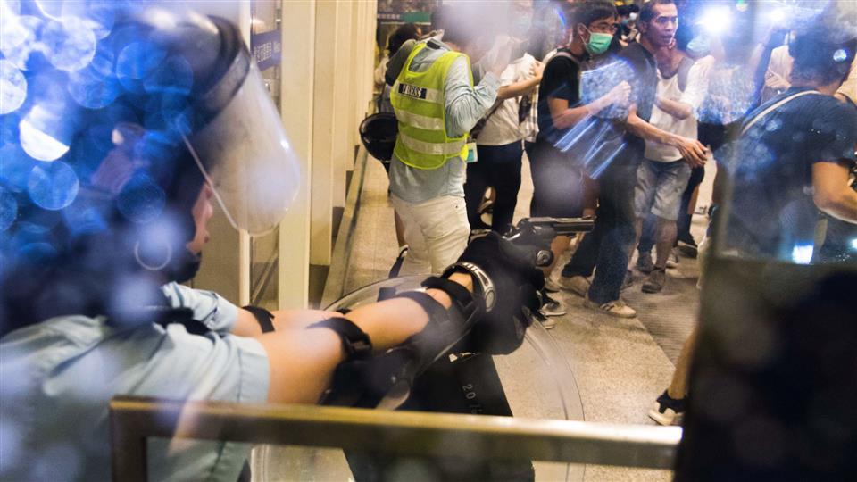 Un policier sort son arme après que les manifestants l'ont battu