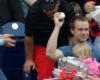 En tenant sa fille et sa nourriture dans les bras, il attrape une balle de baseball
