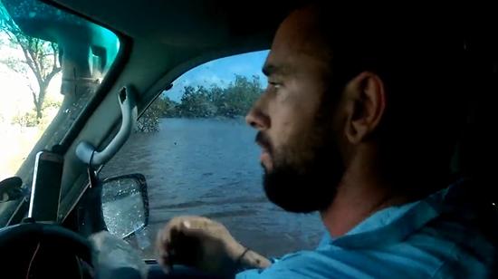 Il conduit son Land Rover 4x4 à travers le lit d'une rivière