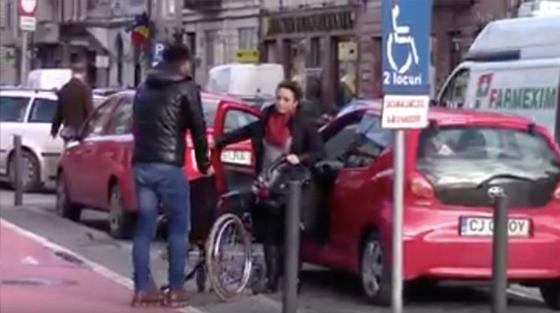 Il attend avec un fauteuil les personnes valides, qui occupent les places des personnes handicapées