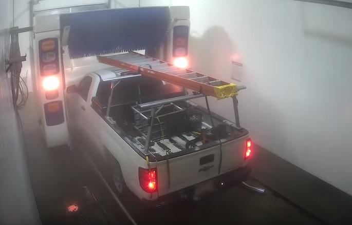 Un pick-up se coince dans un lave-auto avec une échelle attachée sur le toit