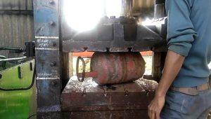 Il écrase les bouteilles de gaz avec une presse hydraulique