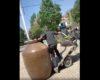 Deux génies essaient de charger un grand pot de terre sur un triporteur